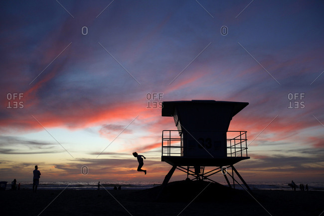 A boy jumps off of a lifeguard stand at sunset at La Jolla Shores Beach in San Diego, CA