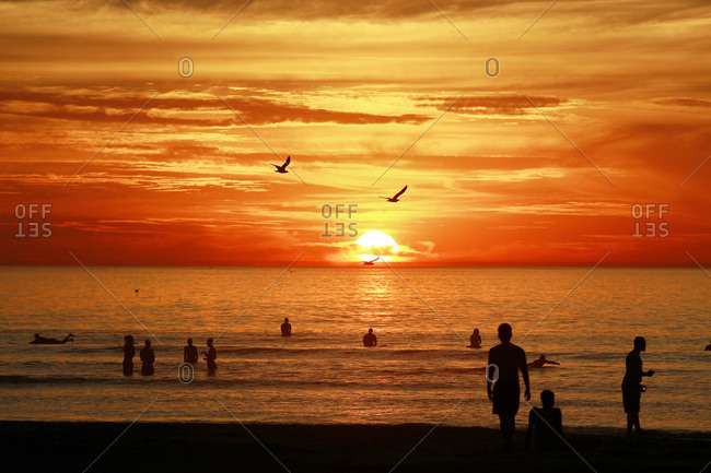 Beach goers and surfers watch as the sun sets at La Jolla Shores Beach in San Diego, California