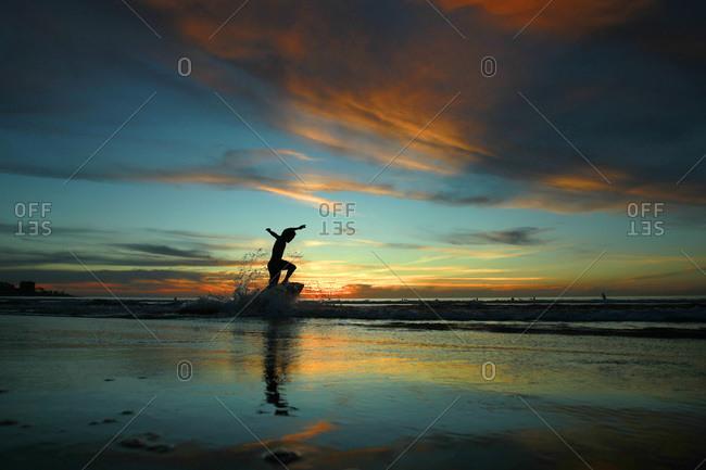 A skim boarder glides across the sand as the sun sets at La Jolla Shores Beach in San Diego, California