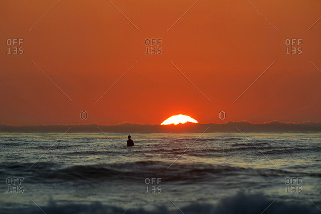 A surfer waits for a wave at sunset at Windansea Beach in La Jolla, a beach community in San Diego, CA