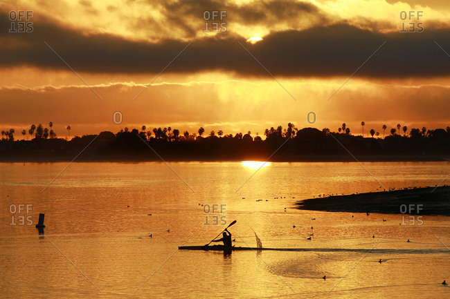 A kayaker glides across the water as the sun sets in Mission Bay in San Diego, CA