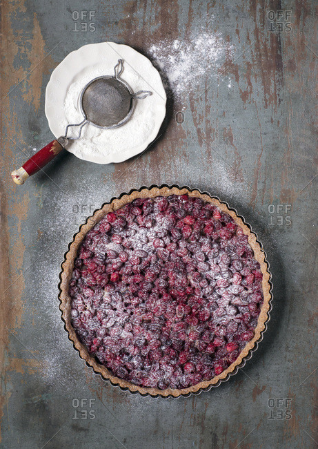 A cranberry tart made with almond and spelt flour crust, sweetened with maple syrup and topped with confectioner's sugar