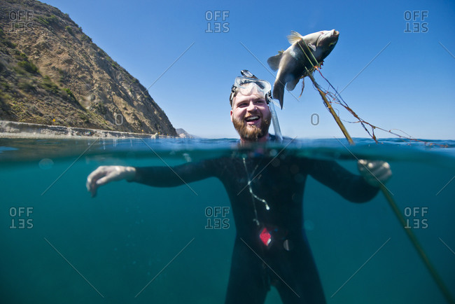A spear fisherman presents his catch off the coast of Catalina Island, CA