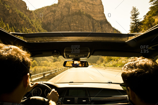 Two friends drive through Glenwood Canyon, Colorado with the sunroof open