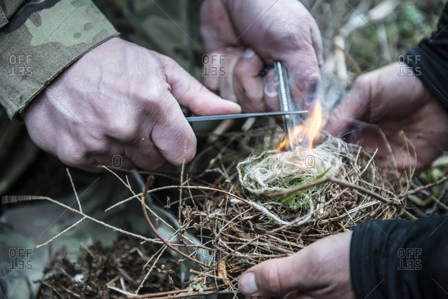 Two people using magnesium to start a fire in the wilderness