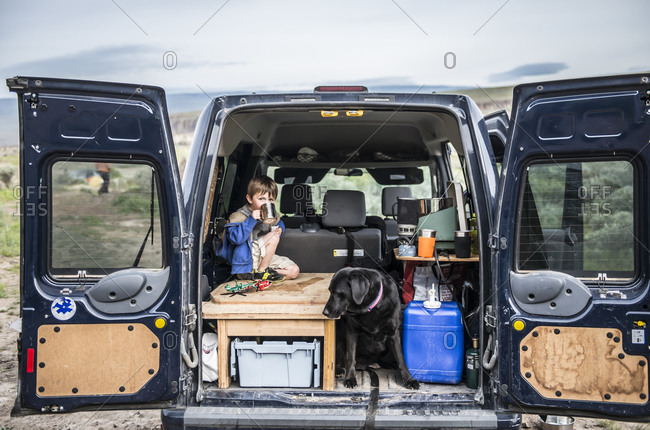 A young boy drinks from a mug while car camping with a dog in Eastern Washington