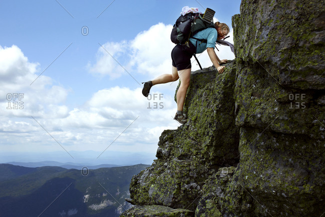 A young female thru hiker climbs a rock ledge in the White Mountains on New Hampshire