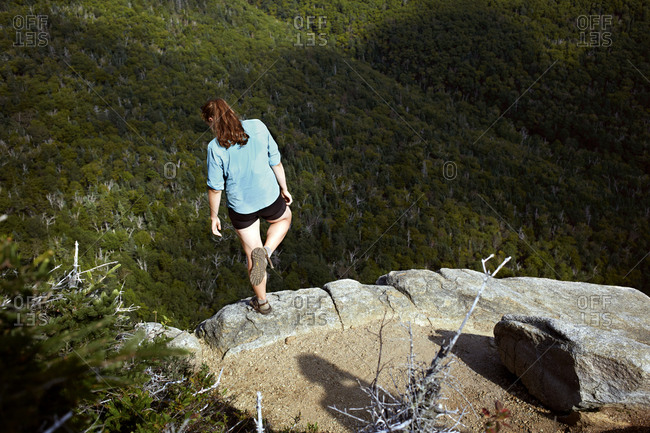 Female hiker stands at the edge of a cliff in New Hampshires White Mountains
