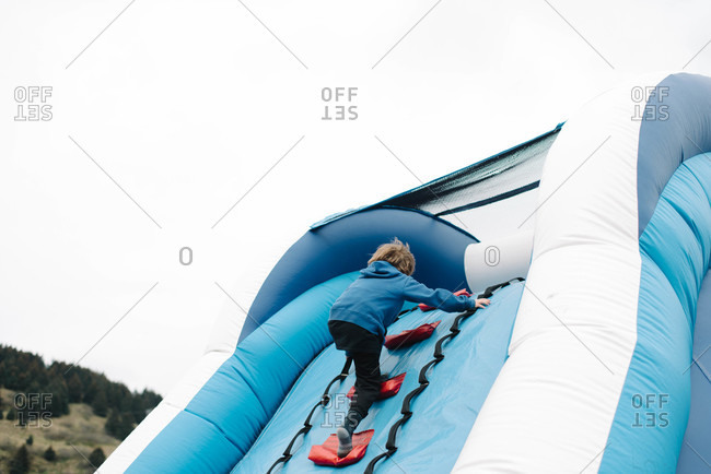 Boy climbing up an inflatable castle