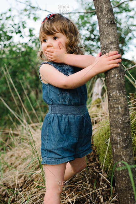 Little girl standing by a tree