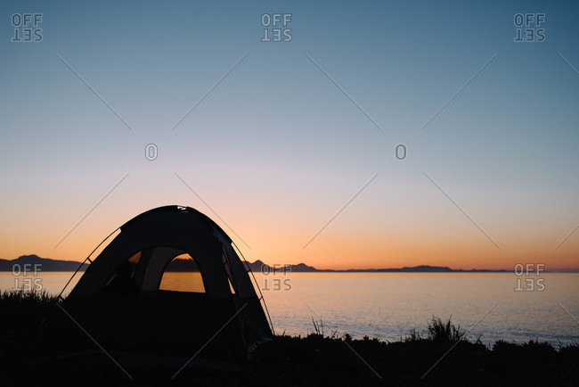 Tent on the shore at sunset