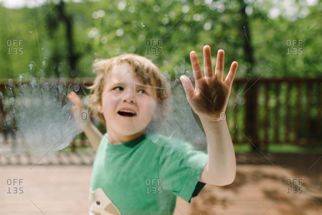 Boy leaving handprints on the window