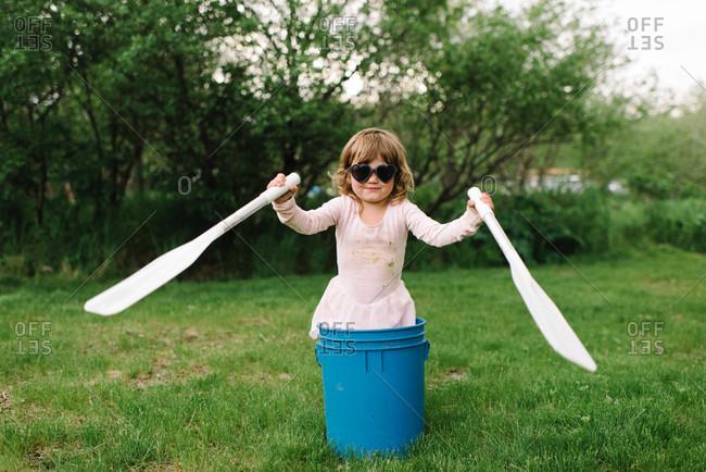Little girl standing in a bucket with oars