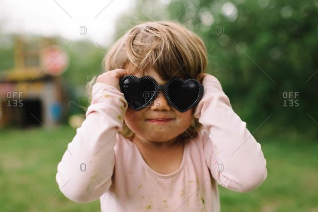 Girl wearing heart-shaped sunglasses