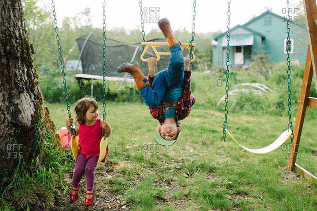 Siblings playing at a swing