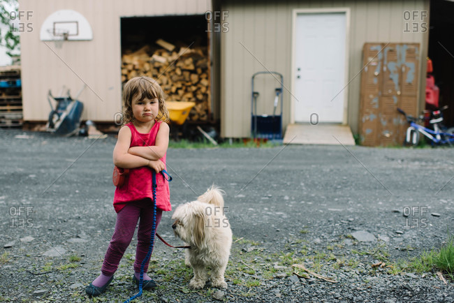 Little girl standing with her dog
