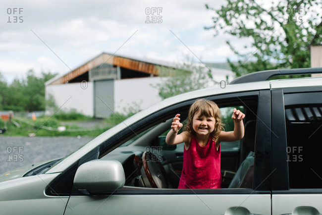Little girl waving from the front seat of a car
