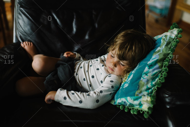 Little girl sleeping in an armchair