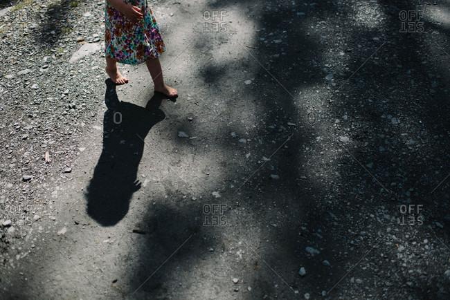 Little girl walking barefoot on a road