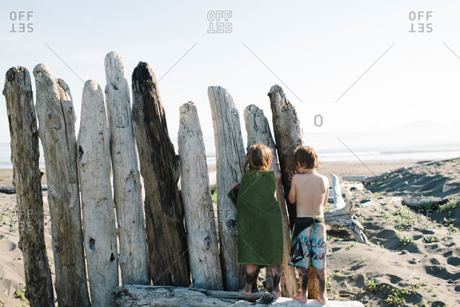 Children hiding behind driftwood on a beach