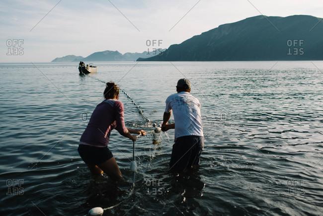 People gathering a fishing net