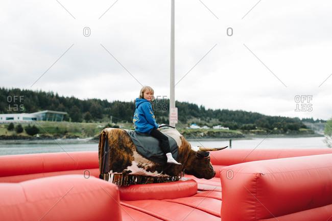 Boy sitting on a mechanical bull