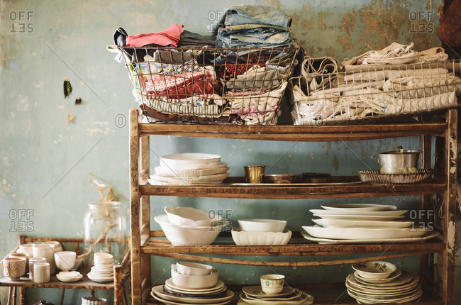 A shelf filled with vintage dishware and linens