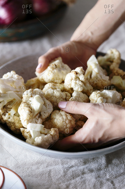 Woman covering cauliflower florets in spicy dressing