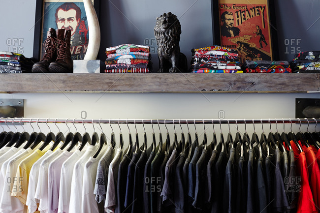 Rack of t-shirts organized by color in a trendy boutique