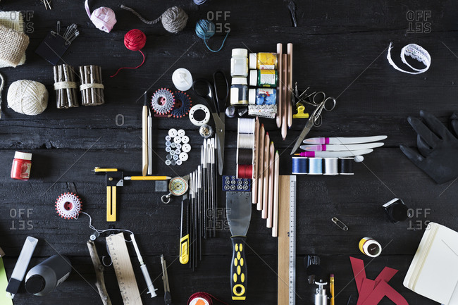 Arrangement of craft materials and tools on black wood