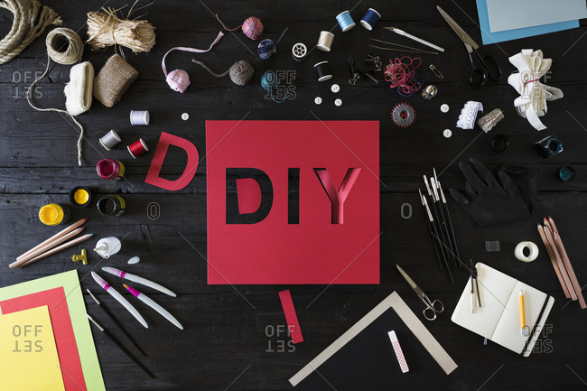 Craft materials, tools and red cardboard with the word DIY on black wood