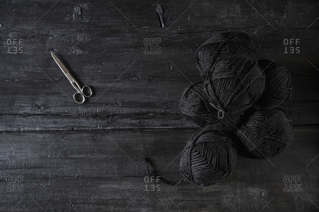 Scissors and balls of black wool on black wood (Monochrome)