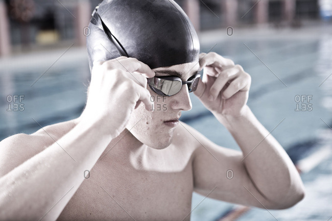 Swimmer in indoor pool putting on swimming goggles