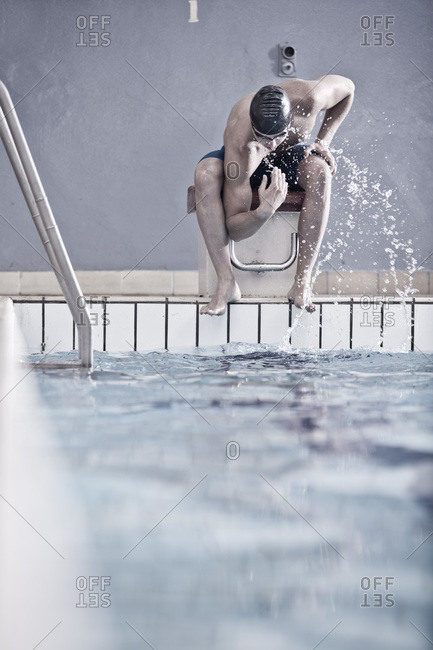 Swimmer splashing water on his face while sitting on starting block