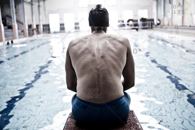 Rear view of a swimmer in indoor pool sitting on starting block