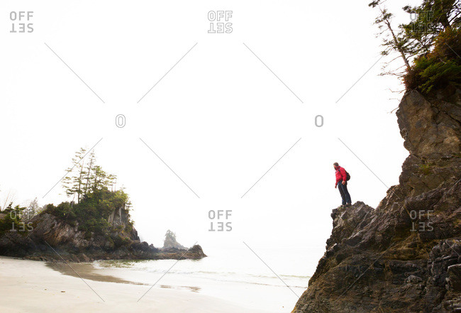 Man standing on a rocky promontory above a beach in British Columbia