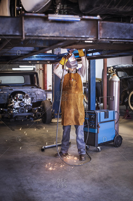 Man in welding mask working on a metal project in workshop