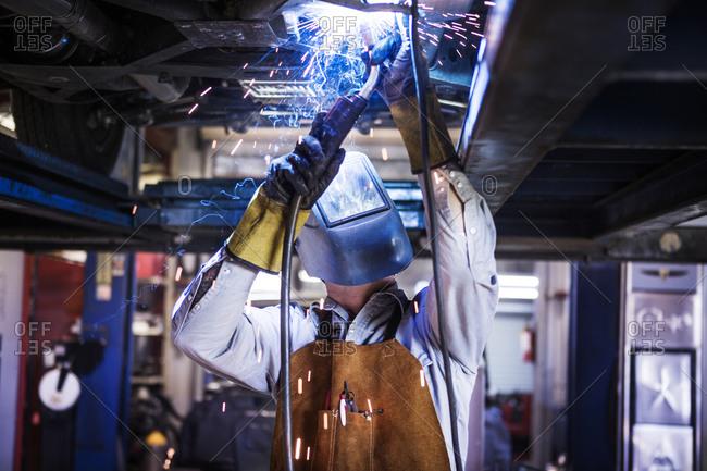 Portrait of a man welding in an auto shop