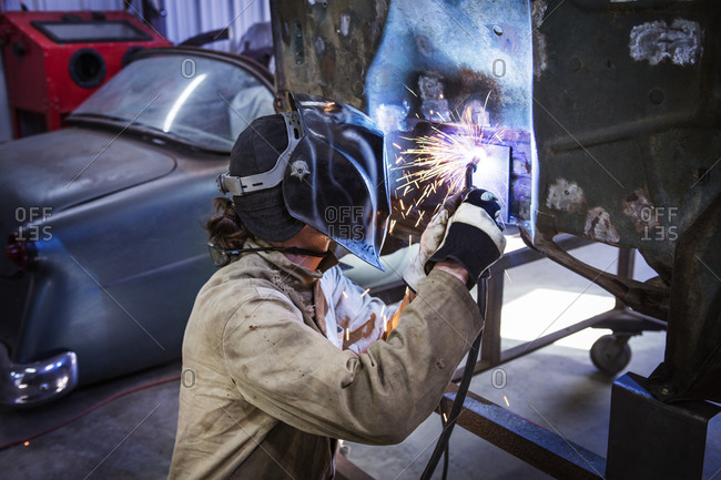 Man welding the body of a vehicle under renovation