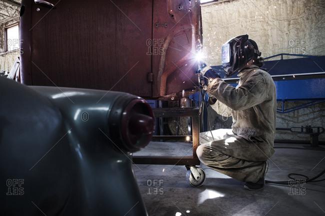 Worker welding truck body in custom vehicle shop