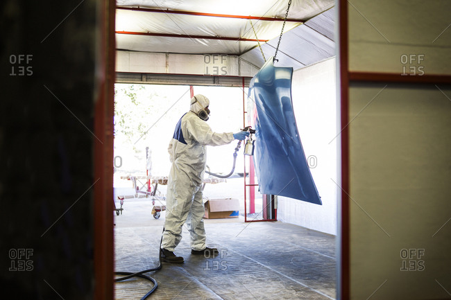 View into spray room of main in protective gear painting the hood of a vehicle