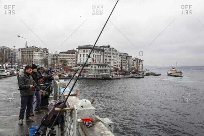 Istanbul, Turkey - November 21, 2014: Locals fishing at the port of Karakoy in Istanbul, Turkey