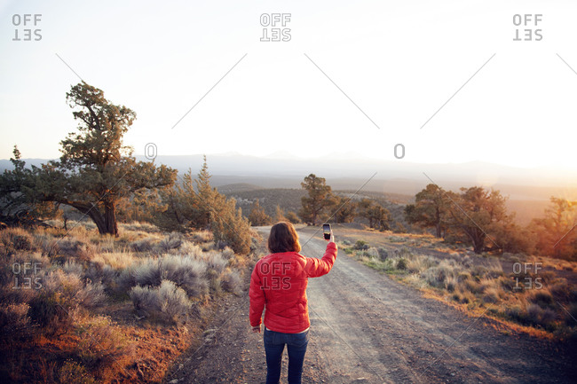 Woman photographing the sunset in Cline Butte, Central Oregon