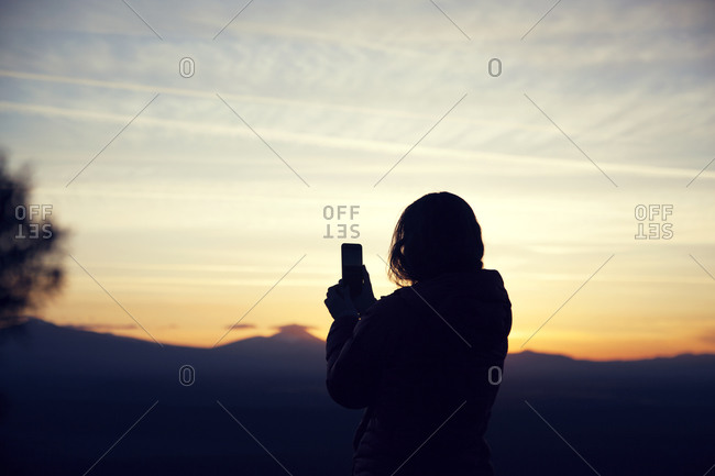 Woman taking a photo of the sunset in Cline Butte, Central Oregon