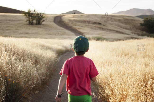 Young boy hiking along a path