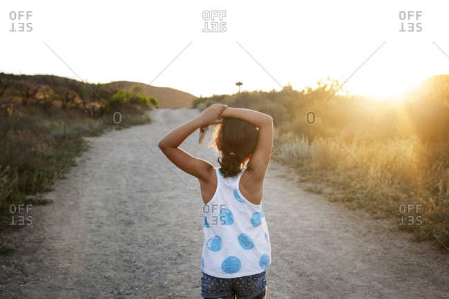 Young girl on a dirt road at sunset
