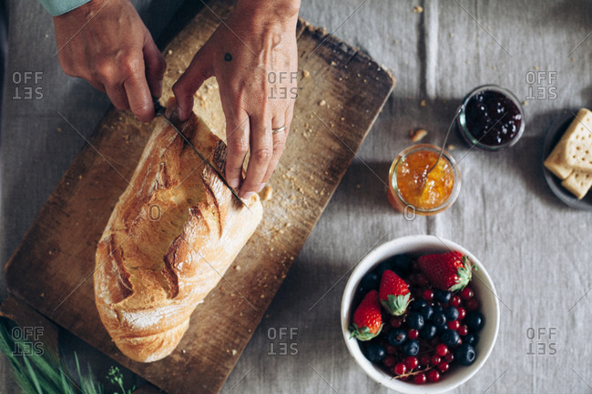 A woman slices a loaf of bread for breakfast