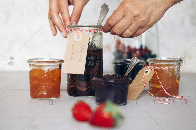 A woman labels homemade jam