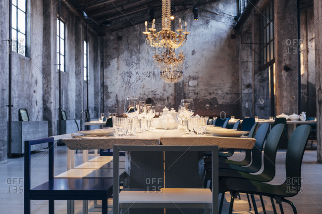 A long table set for dining in a run-down building