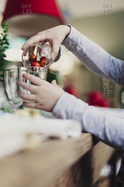 A girl pours cranberries into a glass for a Christmas celebration